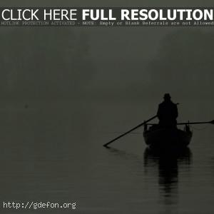 Рыбак в лодке посреди озера