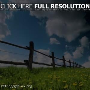 Деревянный забор, одуванчики и облачное небо